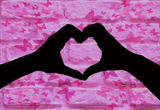 Valentines day, silhouette of two hands making a heart shape together on a pink brick wall with butterfly`s stock photography
