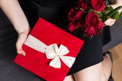 Valentines day surprise - woman holding in hands red gift and rose bouquet royalty free stock images