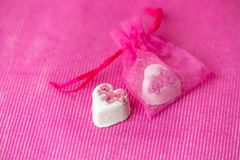 Valentines Day - sweet white heart-shaped chocolates on a pink background royalty free stock photos