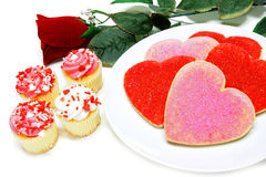 Valentines Day sweets. Heart shaped Valentines Day cookies and cupcakes with rose over white Stock Photos