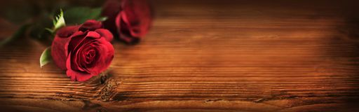 Valentines day with symbolic red roses. Lit on rustic wood Stock Photography