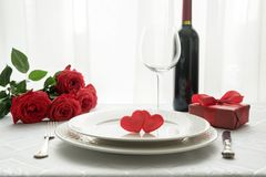 Valentines day table place setting with red roses, gift box, and wine. Invitation for a date. Valentines day table place setting with red roses, gift box, and stock photos