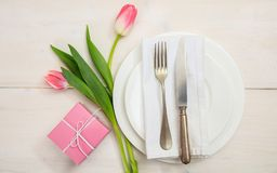Valentines day table setting with pink tulips and a gift on white wooden background. Top view stock images