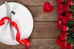 Valentines day table setting with plate, fork, knife, red heart, ribbon and roses.   background Stock Images