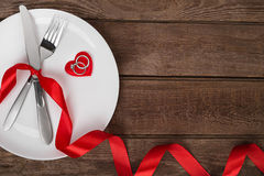 Valentines day table setting with plate, fork, knife, red heart, ring and ribbon.   background Stock Images