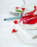 Valentines day table setting with plate, knife, fork, red ribbon Stock Image