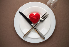 Valentines day table setting with red heart, white plates, fork, knife and wineglass. Stock Image