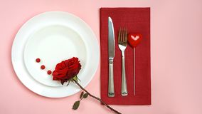 Valentines day table setting with red rose bud, fork and knife heart red tablecloth on pink pastel background. Romantic table royalty free stock photo