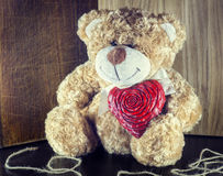 Valentines Day. Teddy Bear Loving cute with red hearts sitting alone. Vintage. Retro romantic styled on wooden background. Copyspase Royalty Free Stock Images