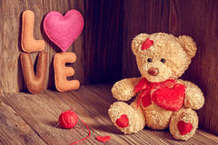 Valentines Day. Teddy Bear Love.Hearts, word Love. Valentines Day. Teddy Bear Loving cute with red hearts sitting alone, Handmade word Love, tangle of sewing Royalty Free Stock Photography