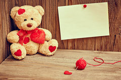 Valentines Day. Teddy Bear Loving. Alone, note. Valentines Day. Teddy Bear Loving with red hearts sitting alone, note and  tangle of sewing thread. Vintage Stock Photos