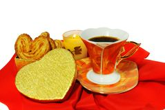 Valentines day theme. A cup of coffee with a box of cookies and a candle on red textile closeup Stock Photography