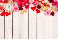 Valentines Day top border of hearts, flowers, gifts and decor on white wood Royalty Free Stock Image