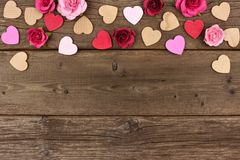 Valentines Day top border of hearts and roses against rustic wood. Valentines Day top border of wooden hearts and paper roses against a rustic wood background Royalty Free Stock Image