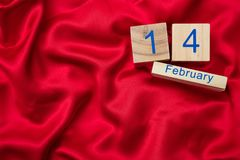 Valentines day. Top view of calendar wooden cubes with 14 February text on red silk background royalty free stock photography