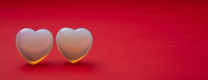 Valentines day. Top view of light blue glass hearts, red background royalty free stock photo