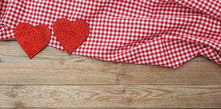 Valentines day. Top view of red fabric hearts, wooden background. Valentines day. Top view of red fabric hearts and checkered white and red cloth against wooden stock photos