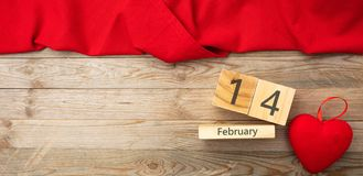 Valentines day. Top view of red heart and calendar date, wooden background. Valentines day. Top view of red heart and calendar wooden cubes with 14 February text stock image