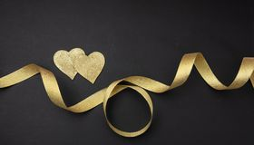 Valentines day. Top view of two golden hearts with satin ribbon against black background. Wallpaper stock photos