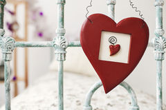 Valentines day toy heart hanging over retro bed on background wi Royalty Free Stock Photo