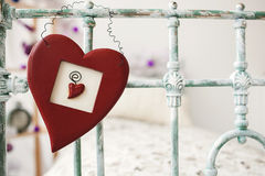Valentines day toy heart hanging over retro bed on background wi Stock Photography