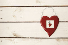 Valentines day toy heart hanging over white wooden background wi Stock Image