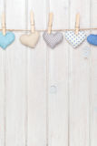 Valentines day toy hearts hanging on rope over white wooden back Stock Images