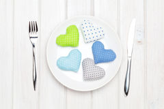 Valentines day toy hearts on plate and silverware. View from abo Royalty Free Stock Photos