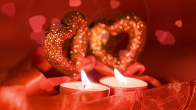 Valentines day,  two candles burning in front of falling hearts, closeup. Valentines day,  two candles burning in front of falling hearts with lens flare effects stock footage