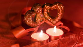 Valentines day,  two candles burning in front of falling hearts, closeup. Valentines day,  two candles burning in front of falling hearts with lens flare effects stock video footage