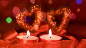 Valentines day,  two candles burning in front of hearts, closeup. Valentines day,  two candles burning in front of hearts and garland blinking on background stock video footage