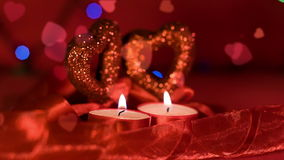 Valentines day,  two candles burning in front of hearts. And garland blinking on background stock video