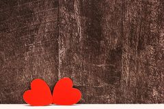 Valentines Day. Two red cardboard hearts are arranged together on a grey wooden background. Concept of love. Copy Space royalty free stock image