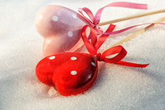 Valentines Day, two red hearts on ice wet snow Royalty Free Stock Photo