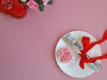 Plate, fork, knife, marzipan rose on pink background. stock image