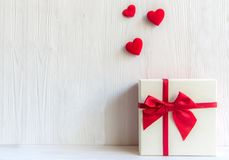 Valentines day white gift box with a red bow on white wall background,