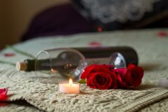 Valentines Day Wine and roses on bed with tea light