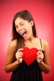 Valentines day woman. Woman holding Valentines Day heart sign. Beautiful mixed race asian / caucasian model Royalty Free Stock Photos