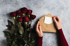 Valentines day woman hand holding envelope love letter with greeting card mothers day. Red rose gift surprise on grey background with copyspace. Love flower Royalty Free Stock Photo