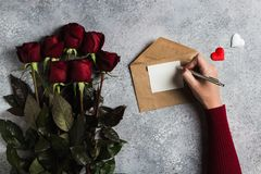 Valentines day woman hand holding pen writing love letter with greeting card. Mothers day red rose gift surprise on grey background with copyspace. Love flower Stock Photography