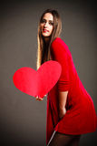 Valentines Day woman holding heart. Valentines Day. Woman in red dress holding heart sign love symbol on grey background in studio Stock Photos