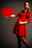 Valentines Day woman holding heart. Valentines Day. Woman in red dress holding heart sign love symbol on grey background in studio Royalty Free Stock Images