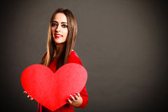 Valentines Day woman holding heart. Valentines Day. Woman holding heart sign with copy space on grey background in studio Stock Photo