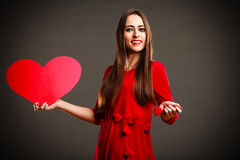 Valentines Day woman holding heart. Valentines Day. Woman wearing red dress holding big heart sign love symbol on grey background Royalty Free Stock Photos