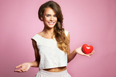 Valentines Day. Woman holding Valentines Day heart sign with copy space. Pink background model and heart Royalty Free Stock Photos