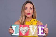 Valentines Day. Woman wearing yellow dress holding sign love sym Royalty Free Stock Images