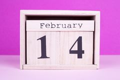 Valentines Day wooden date. February 14th on pink background. Favorite holiday of love stock image