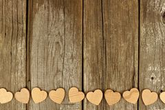 Valentines Day wooden hearts bottom border on rustic wood Stock Photos