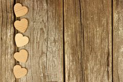 Valentines Day wooden hearts bottom border on rustic wood Stock Images