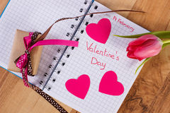 Valentines Day written in notebook, fresh tulip, wrapped gift and hearts, decoration for Valentines Stock Photo